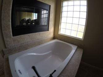 Master bath with grand soaker bathtub and recessed fireplace